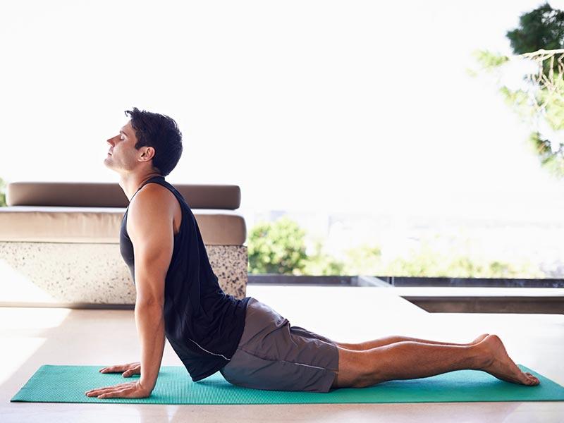 joven haciendo posición de yoga perro hacia abajo